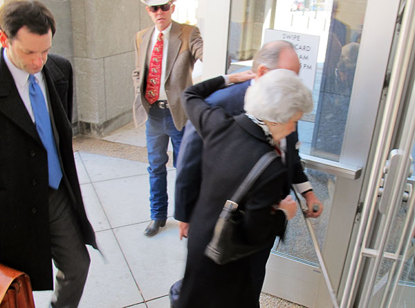 Mary Ferguson supports her husband, Allen Mead Ferguson, as they enter the courthouse on West Broad Street for his sentencing.