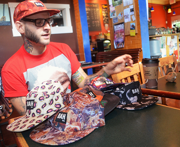 Neil Thomas, 30, designs five-panel caps from his Oregon Hill home. (Photo by Mark Robinson)