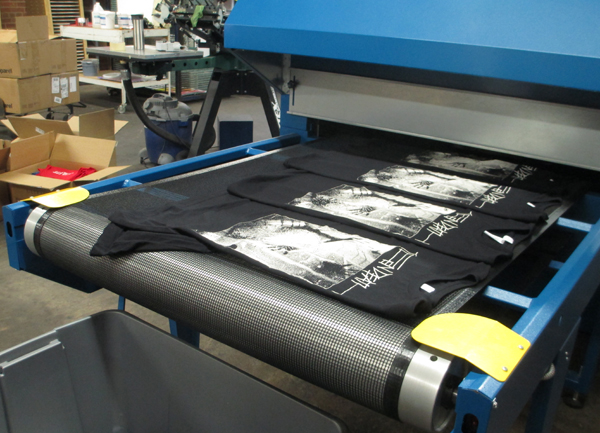 The conveyor belt dryer that cures the ink into shirts.