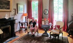 William Lipps and his Boston terrier, Ena, enjoy the home's formal parlor. Photo by Brandy Brubaker.