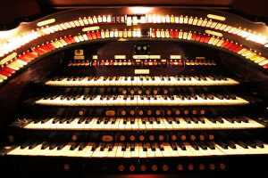 The organ console is raised from below the stage and controls instruments hidden above the theater.