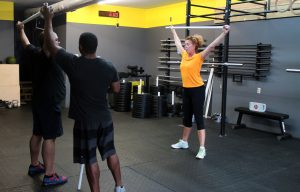 A trainer works with a two-person class in the new CrossFit gym.