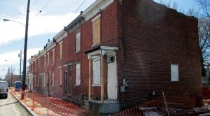 The developer has scraped off brightly colored paint off the brick structure.