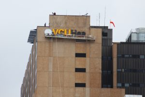 Crews lift up the new sign on the Medical Center.