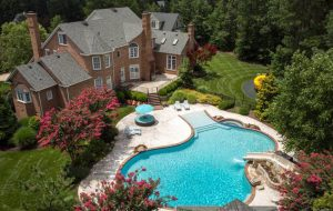 The property features a walk-in heated pool with a hot tub, stone feature with a water slide, and nearly 300-square-foot pool house. (Courtesy CVRMLS)