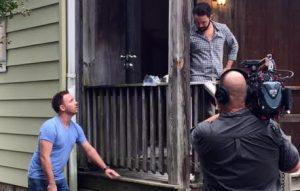 Josh Romano discusses the deck to be removed with a crew member during filming. (Courtesy Breese Romano)