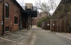 NFA's original suit claims the parking spaces (left), dumpsters (right) and the above HVAC deck are obstructing access to their property ahead. (J. Elias O'Neal)