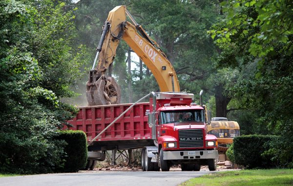 Crews pile debris into a dump truck on the property at 101 S. Ridge Road. (Jonathan Spiers)