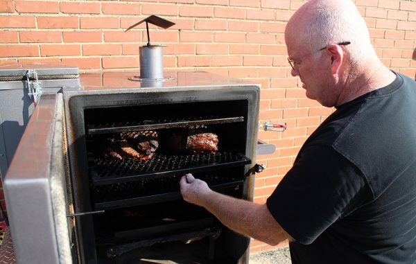 Roby Williams tends to pork butts that have smoked for eight hours at Smohk in Scott's Addition. (J. Elias O'Neal)