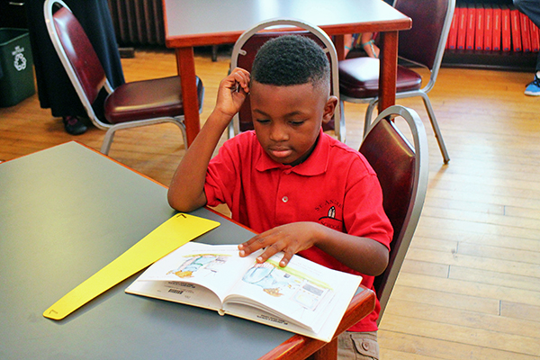 First-grader Jeremiah Jones reads a book in the St. Andrew's School library. Photos by Brandy Brubaker.