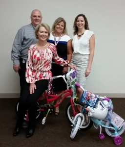 West Broad Village reps Kendall Rumsey, Tammy Philblad, and Melody Thomas present bikes to Virginia Homes for Boys and Girls President Claiborne Mason.