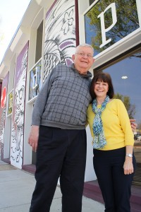 The pair in front of their downtown office, with its tattooed exterior behind them.
